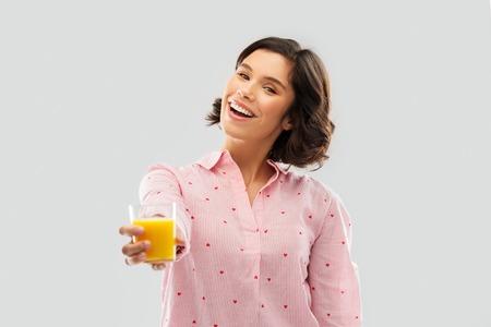 happy young woman in pajama holding orange juice