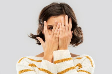 Jeune femme regardant par un œil à travers ses doigts