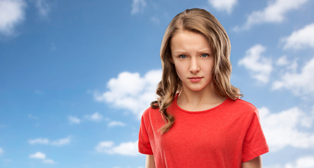 sad or angry teenage girl in red t-shirt over sky