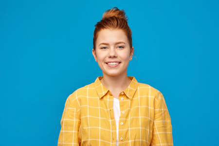 smiling red haired teenage girl in checkered shirt