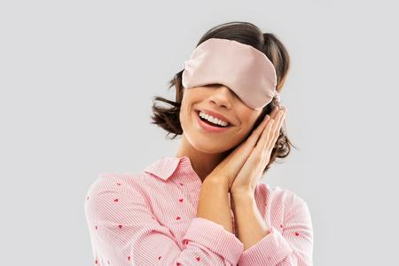 gelukkige jonge vrouw in pyjama en oogslaapmasker Stockfoto