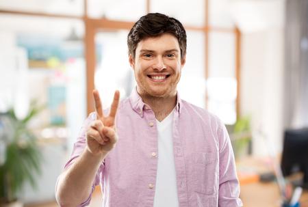 homme montrant deux doigts ou la paix au-dessus de la salle de bureau Banque d'images