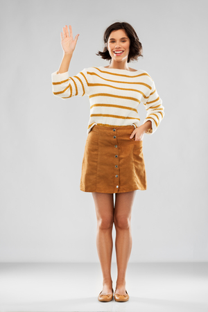 woman in pullover, skirt and shoes waving hand