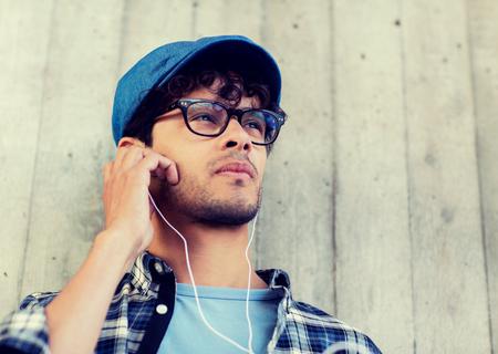 gente, música, ocio y estilo de vida - hombre con auriculares escuchando música en la calle Foto de archivo