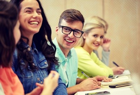 concepto de educación, escuela secundaria, universidad, visión y personas - hombre joven en anteojos con un grupo de estudiantes en una conferencia