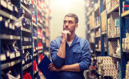autoservice, reparatie, onderhoud en mensenconcept - automonteur of smid met klembord in werkplaats of magazijn Stockfoto