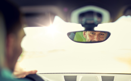 road trip, transport and people concept - rearview mirror reflection of man driving car 版權商用圖片