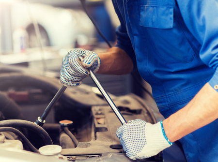 car service, repair, maintenance and people concept - auto mechanic man with wrench and lamp working at workshop 版權商用圖片