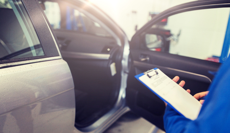 car service, repair, maintenance and people concept - auto mechanic man or smith with clipboard at workshop 스톡 콘텐츠