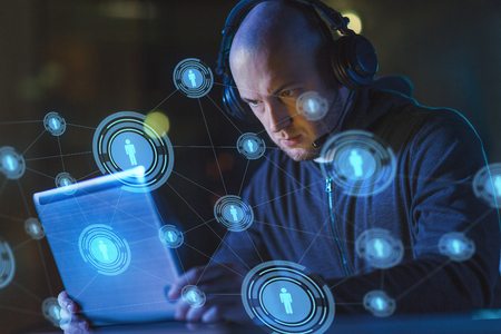 cybercrime, hacking and technology concept - male hacker with headset using laptop computer for cyber attack or wiretapping in dark room Stock Photo