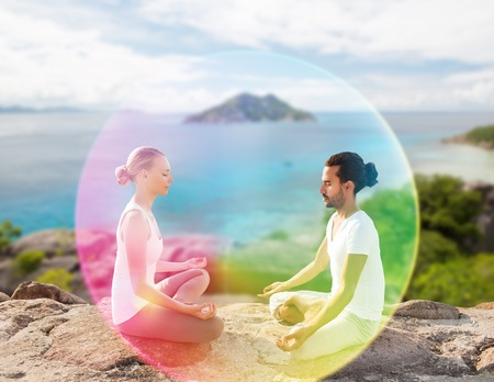 couple doing yoga in lotus pose with rainbow aura Reklamní fotografie