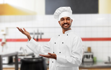 happy male indian chef at restaurant kitchen
