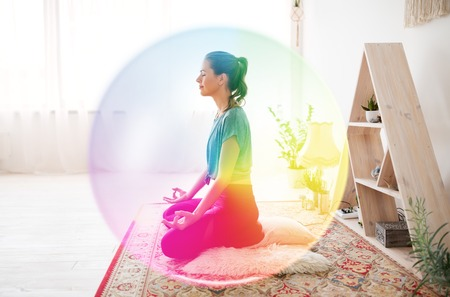 mindfulness, spirituality and healthy lifestyle concept - woman meditating in lotus pose at yoga studio over rainbow aura Imagens
