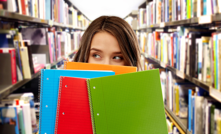 teenage student girl behind notebooks at library