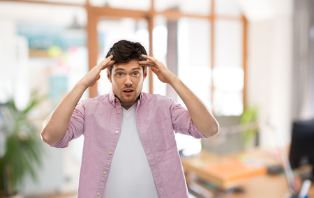 man touching his head over office room