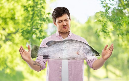 displeased young man showing size of fish 写真素材