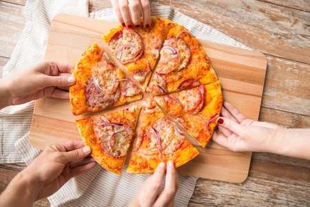 close up of hands sharing pizza on wooden table Imagens
