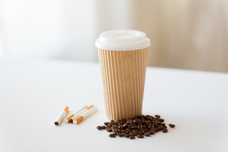 close up of cigarettes, coffee cup and beans 免版税图像
