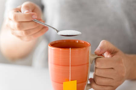 close up of woman adding sugar to cup of tea Stock fotó - 120796434