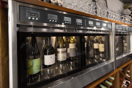 close up of wine bottles in dispenser at bar