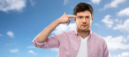 bored man shooting himself by finger gun gesture