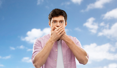 shocked man covering mouth by hands over blue sky