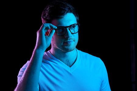man in glasses over neon lights in dark room 스톡 콘텐츠