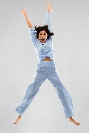 happy woman in blue pajama jumping high