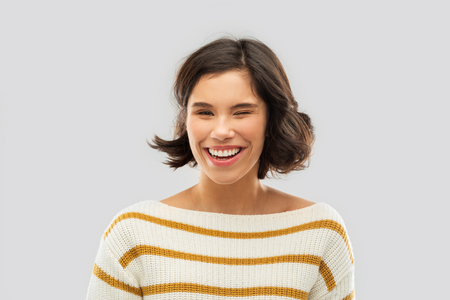 happy smiling woman in striped pullover winking