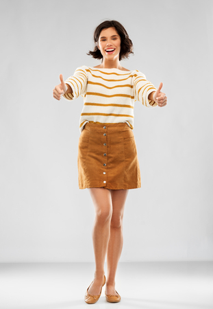woman in pullover, skirt and shoes shows thumbs up Stockfoto