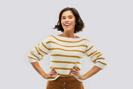 smiling woman in pullover with hands on hips