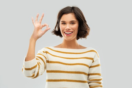 happy smiling woman in striped pullover showing ok Stock Photo