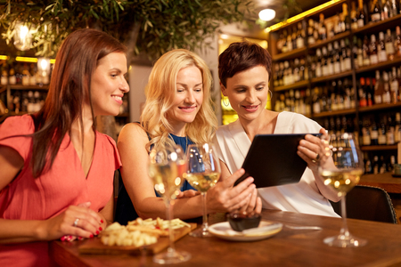 women with tablet pc at wine bar or restaurant