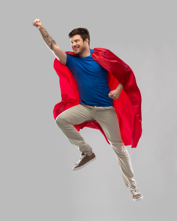 man in red superhero cape flying in air