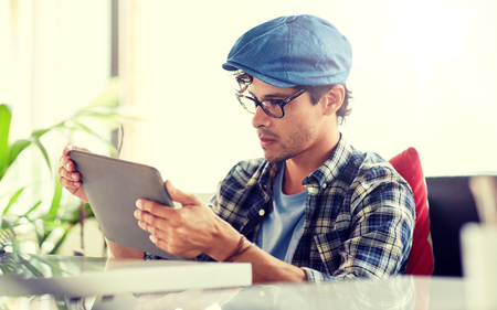 man with tablet pc sitting at cafe table