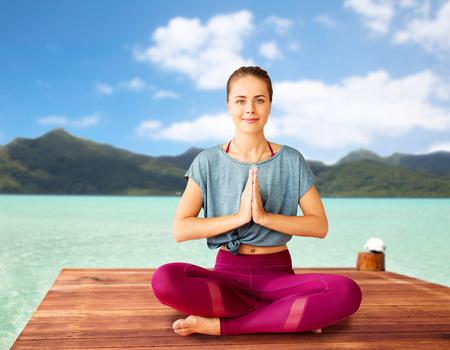 woman doing yoga and meditating in lotus pose Reklamní fotografie - 120497491