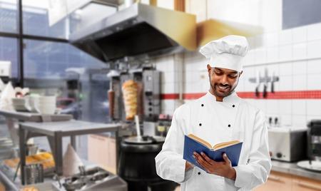 happy indian chef reading cookbook at kebab shop