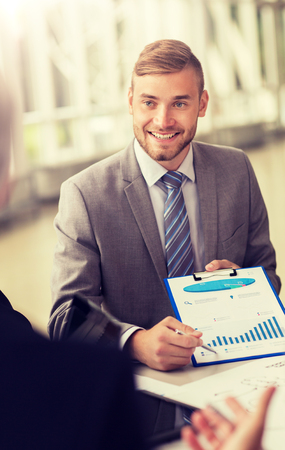 smiling businessman with graph at business meeting
