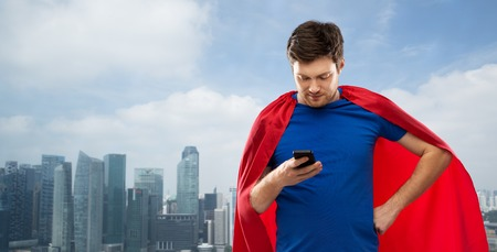 man in superhero cape using smartphone over city
