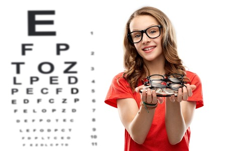 teenage girl holding glasses over eye test chart Stock fotó