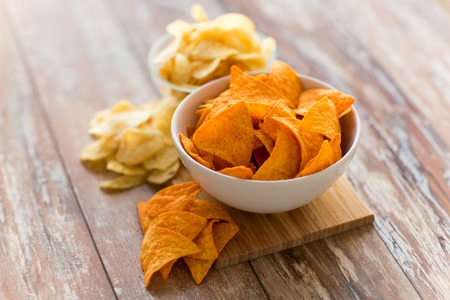 close up of potato crisps and nachos in bowls