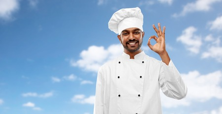 happy male indian chef in toque showing ok gesture Imagens