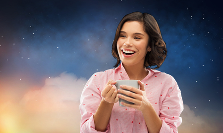 happy woman in pajama with mug of coffee at night