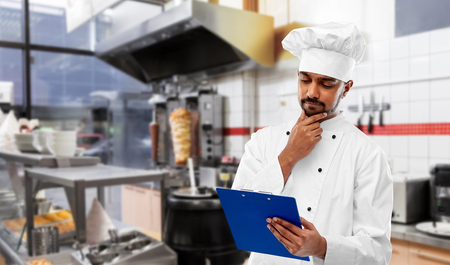 indian chef with menu on clipboard at kebab shop Stock Photo - 120495963