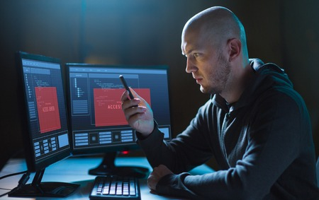 hacker with smartphone and computers in dark room