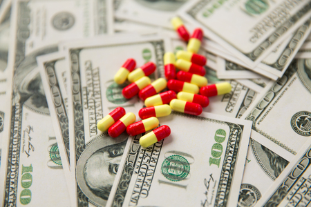 close up of pills or drugs and dollar cash money Stock Photo