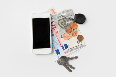 close up of smartphone, euro money and keys
