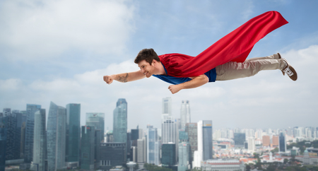 man in red superhero cape flying in air over city