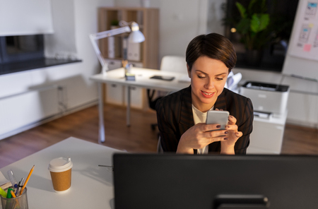 businesswoman using smartphone at night office