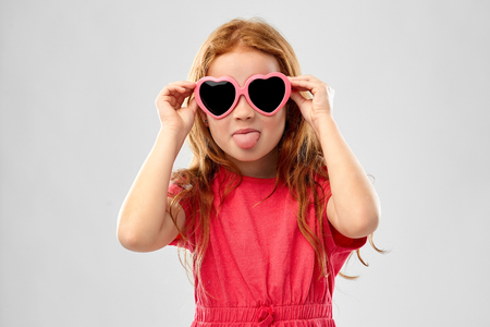 naughty red haired girl in heart shaped sunglasses Stock Photo